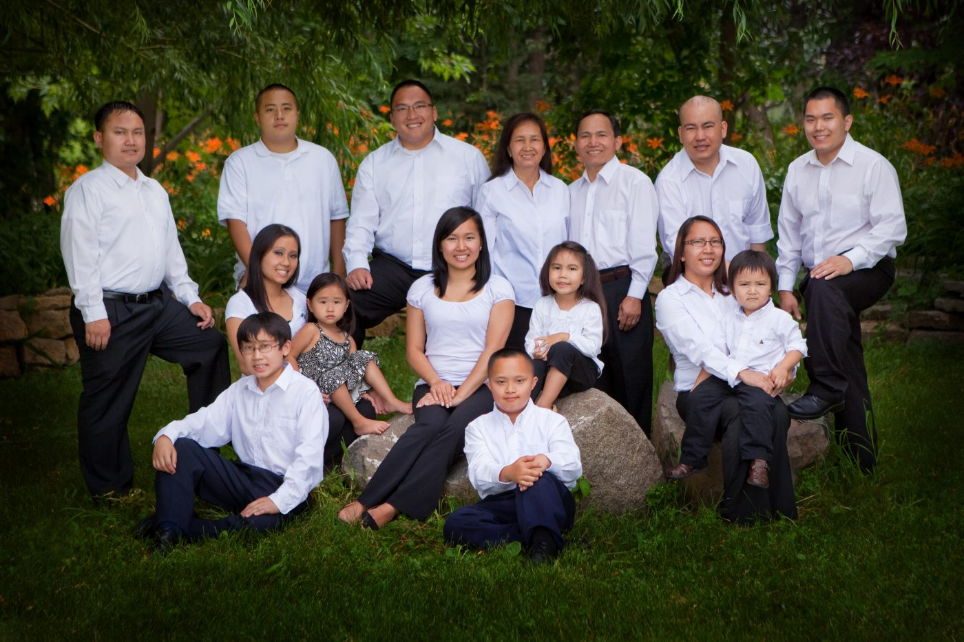 Family of 15 in white shirts and jeans in a garden setting